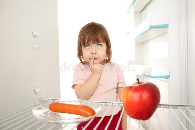 Healthy eating choice. Cute young girl looking in open refrigerator deciding between healthy apple and unhealthy hot dog royalty free stock photography