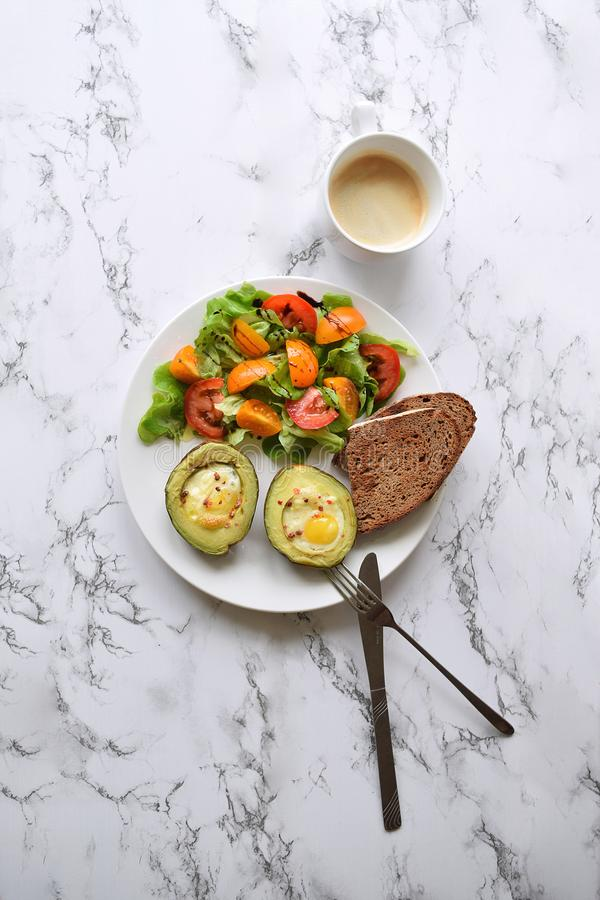 Healthy eating concept Baked avocado with quail eggs royalty free stock image