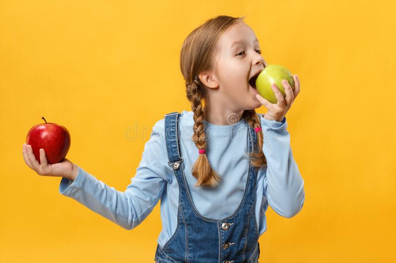 Healthy eating concept. A child bites an apple. Little girl on a yellow background royalty free stock photography