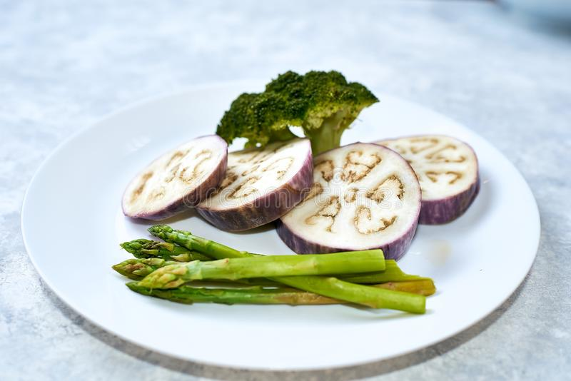 Healthy eating concept. Steamed vegetables in a white plate on a blue table. Eggplant, broccoli, asparagus. Steamed vegetables in a white plate on a blue table stock photos