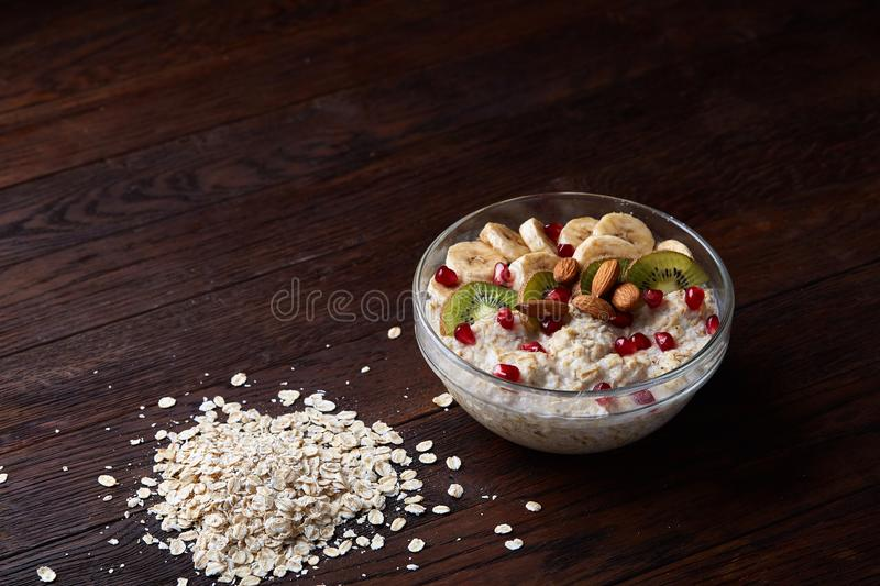 Healthy eating concept bowl of oatmeal cereal and pile of oatmeal over wooden background, selective focus royalty free stock image
