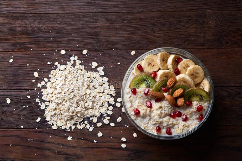 Healthy eating concept bowl of oatmeal cereal and pile of oatmeal over wooden background, selective focus stock photography