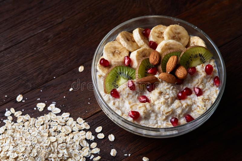 Healthy eating concept bowl of oatmeal cereal and pile of oatmeal over wooden background, selective focus stock images