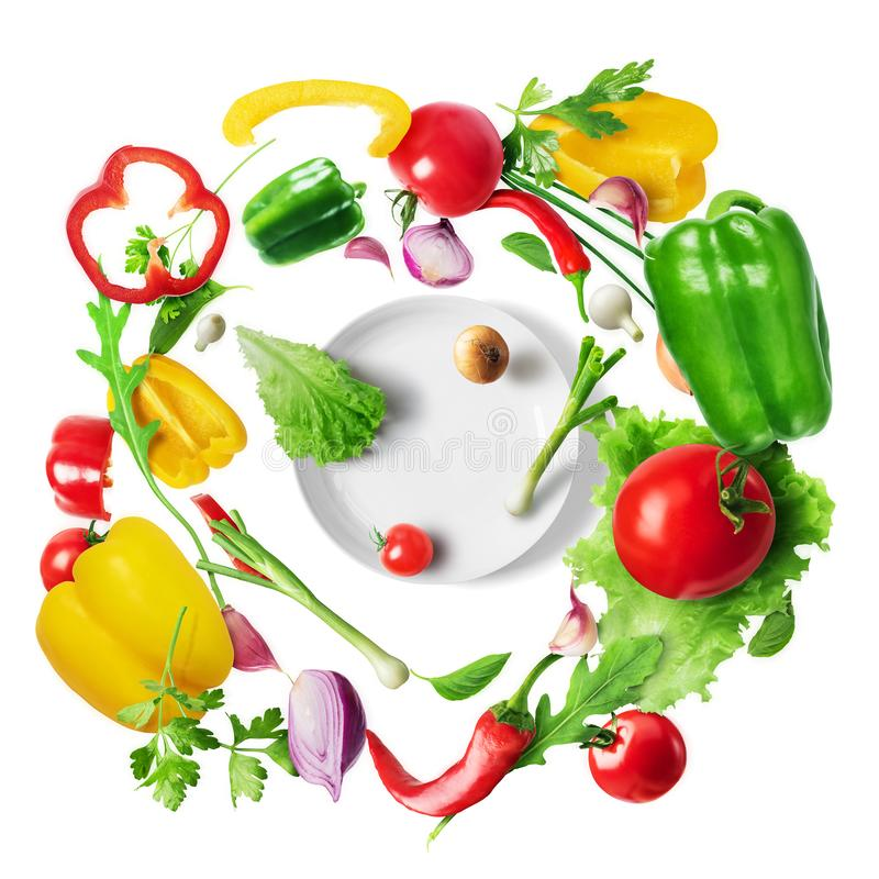 Vegetables flying in a whirl for a salad over a plate isolated on white background. Top view. Healthy eating concept. Vegetables flying in a whirl for a salad stock photos