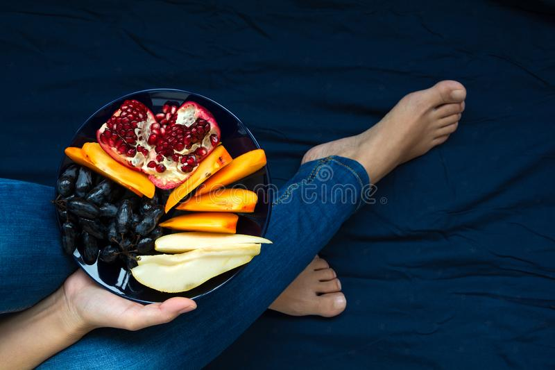 Healthy eating concept. Woman`s hands holding plate with pears, grapes, persimmon and pomegranate fruits. Top view stock photo