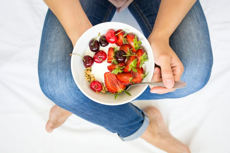 Healthy eating concept. Women`s hands holding bowl with muesli, yogurt, strawberry and cherry. Top view. Lifestyle royalty free stock photos