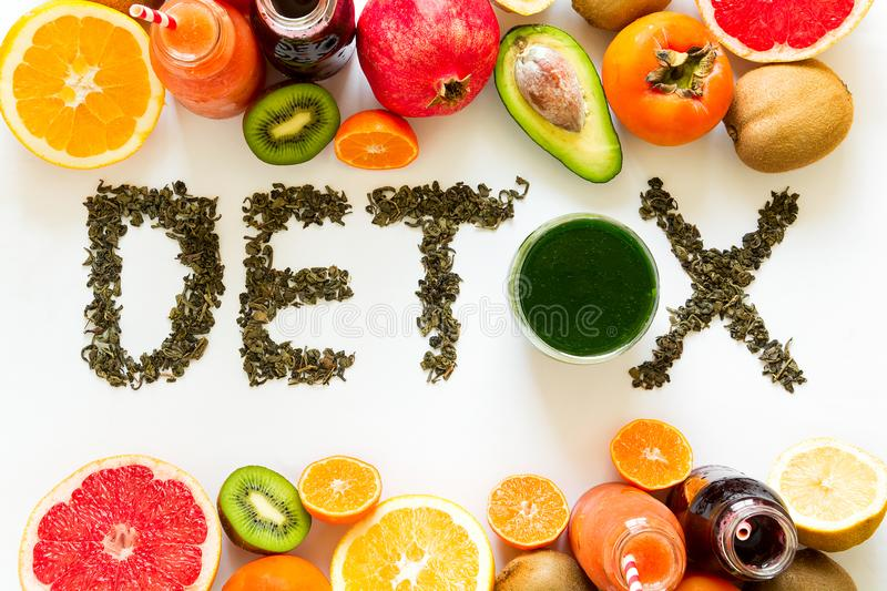 Healthy eating concept. Word `detox` from green tea with colorful smoothies and fruits. Top view royalty free stock image