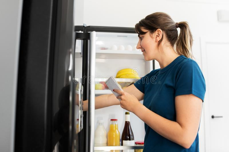 Woman making list of necessary food at home fridge stock images