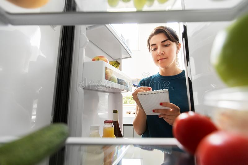 Woman making list of necessary food at home fridge royalty free stock images