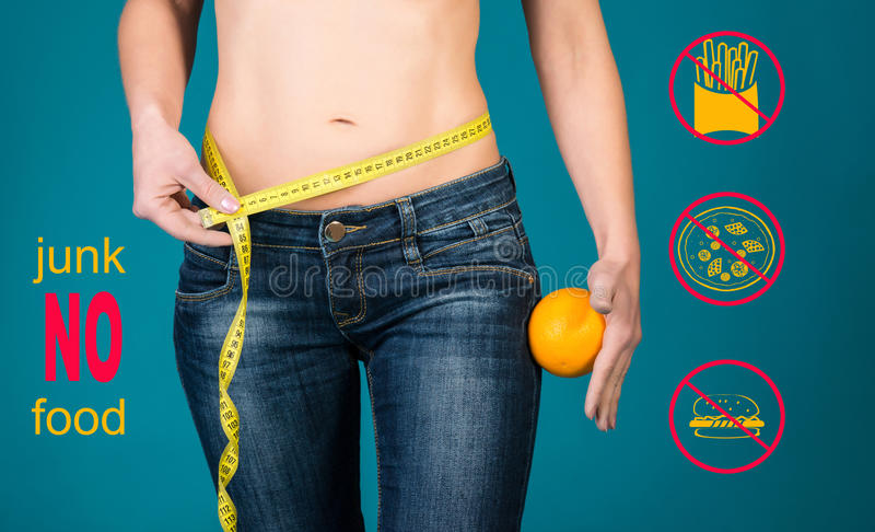 Healthy eating, diet and fitness concept. No junk food. Healthy female body with orange and measuring tape. stock photo