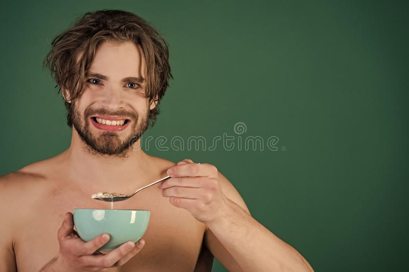 Healthy eating. Dieting and fitness, calorie. Man with wet hair eat breakfast on green background. Food and beauty, health. man with muscular body eating stock photography