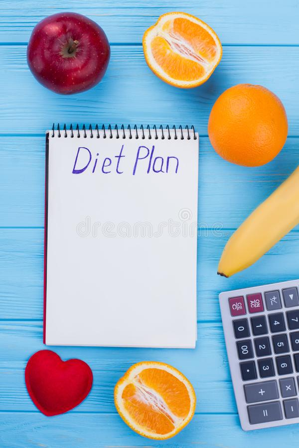 Healthy eating, dieting, slimming and weight loss concept. Fruits, calculator and notepad with inscription diet plan. Balanced fruit diet and health care royalty free stock photos