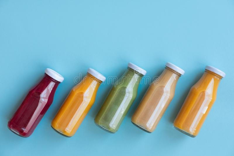 Healthy eating, drinks, diet and detox concept - close up of five bottles with different fruit or vegetable juices for detox plan. Healthy eating, drinks, diet royalty free stock photos