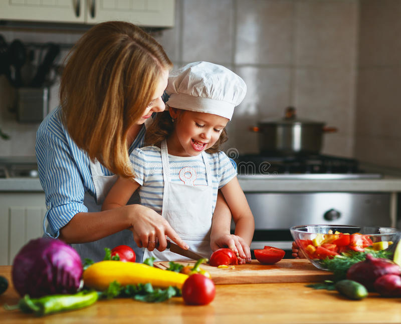 Healthy eating. family mother and child girl preparing vegetarian vegetable salad at home in kitchen. Healthy eating. Happy family mother and child girl stock images