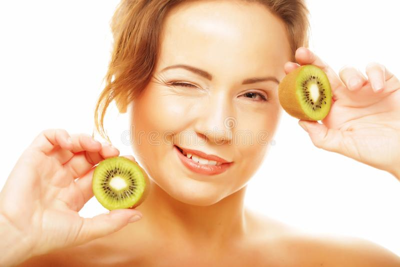 Healthy eating, food and diet concept - Charming young woman holding fresh juicy kiwi and smiles. stock images