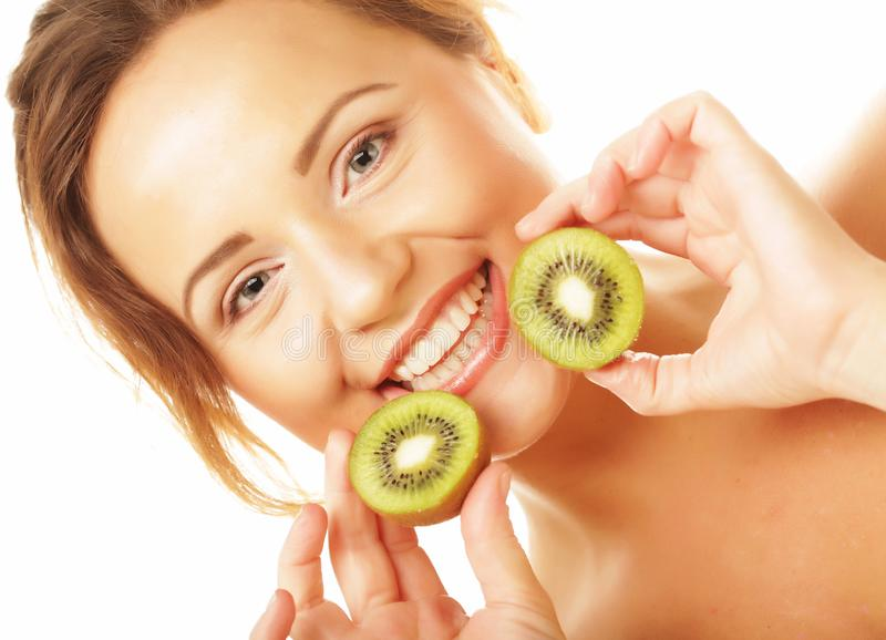 Healthy eating, food and diet concept - Charming young woman holding fresh juicy kiwi and smiles. stock photo
