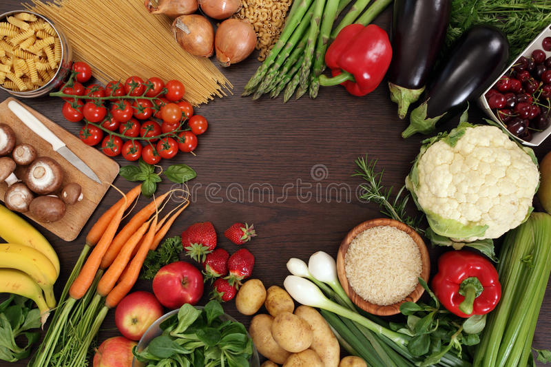 Healthy eating frame. Photo of a table top full of fresh vegetables, fruit, and other healthy foods with a space in the middle for text royalty free stock photo
