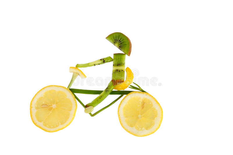 Healthy eating. Funny little man of the kiwi slices. Rides a bicycle made out of a lemon royalty free stock images