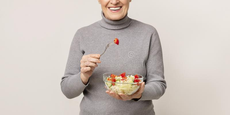 Healthy eating. Happy aged woman holding bowl of vegetable salad royalty free stock images
