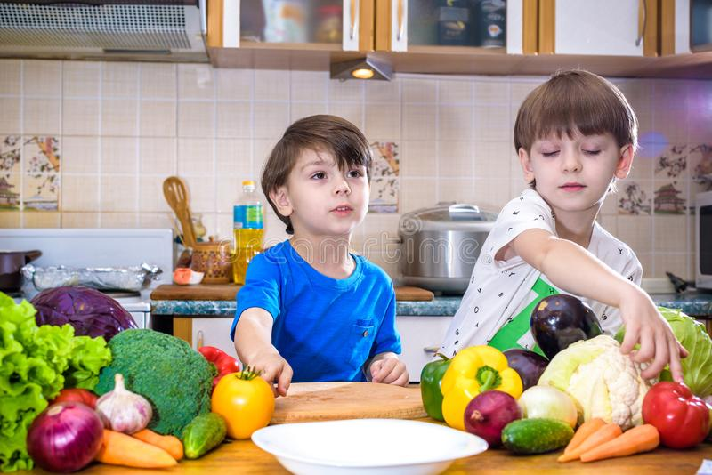 Healthy eating. Happy children prepares and eats vegetable salad. In kitchen. Health and friendship concept royalty free stock image