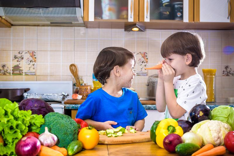 Healthy eating. Happy children prepares and eats vegetable salad. In kitchen. Health and friendship concept royalty free stock photography
