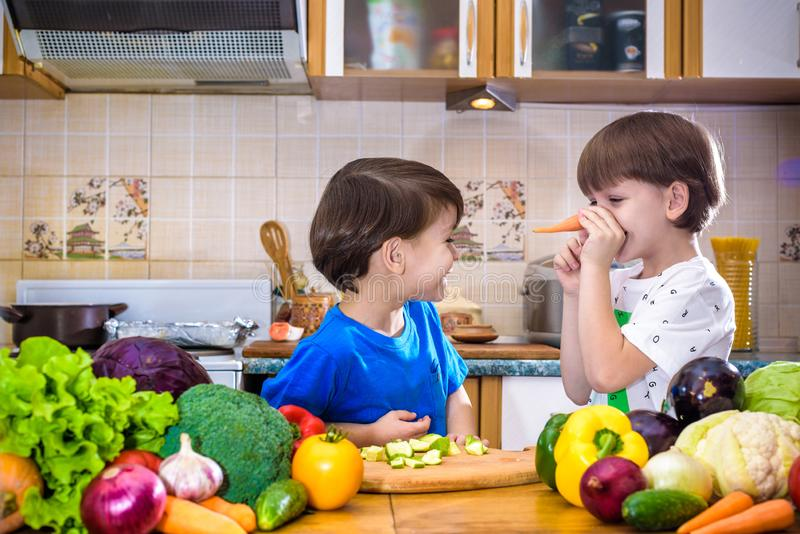 Healthy eating. Happy children prepares and eats vegetable salad. In kitchen. Health and friendship concept royalty free stock photo