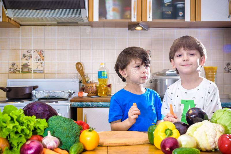 Healthy eating. Happy children prepares and eats vegetable salad. In kitchen. Health and friendship concept royalty free stock images