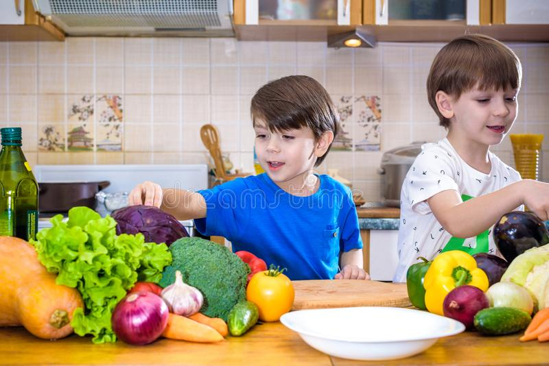 Healthy eating. Happy children prepares and eats vegetable salad. In kitchen. Health and friendship concept royalty free stock photos
