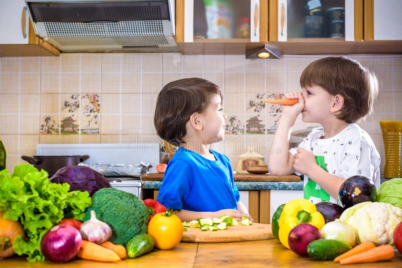 Healthy eating. Happy children prepares and eats vegetable salad. In kitchen. Health and friendship concept stock photo