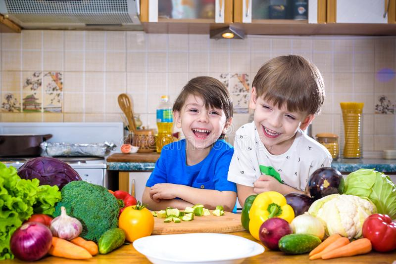 Healthy eating. Happy children prepares and eats vegetable salad. In kitchen. Health and friendship concept stock photos