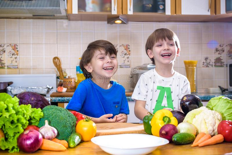 Healthy eating. Happy children prepares and eats vegetable salad in kitchen. Health and friendship concept royalty free stock photos