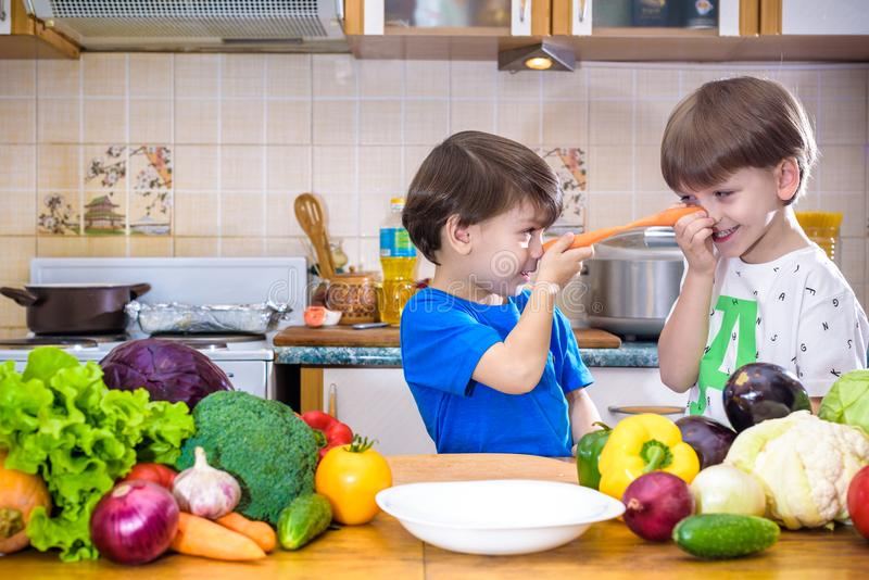 Healthy eating. Happy children prepares and eats vegetable salad in kitchen. Health and friendship concept royalty free stock photography