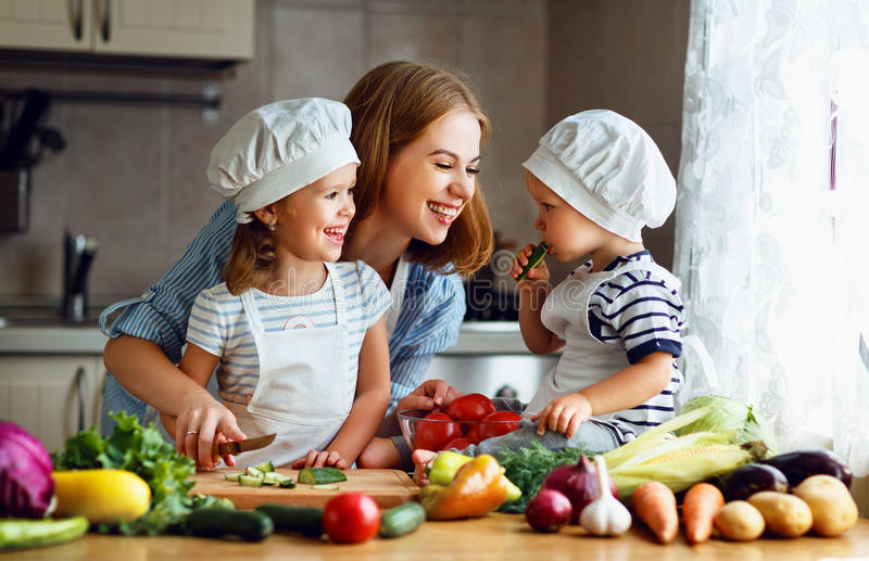Healthy eating. Happy family mother and children prepares veget. Able salad in kitchen stock image