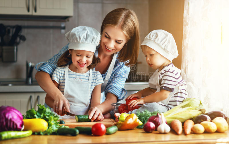 Healthy eating. Happy family mother and children prepares veget. Able salad in kitchen royalty free stock images