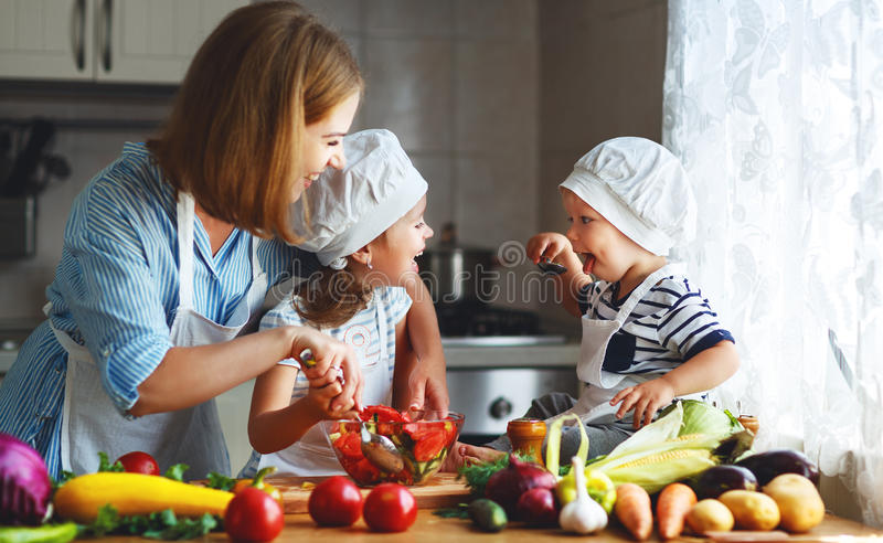 Healthy eating. Happy family mother and children prepares veget. Able salad in kitchen royalty free stock photos