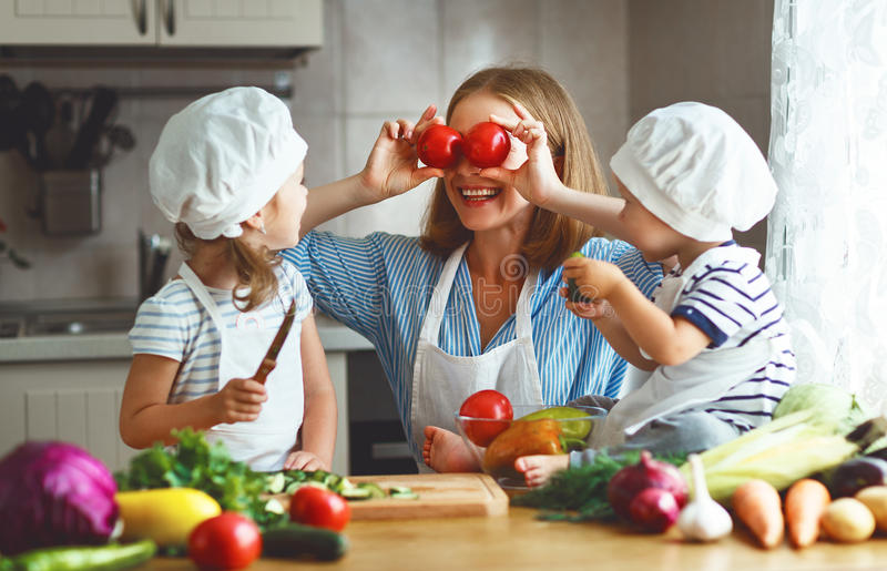 Healthy eating. Happy family mother and children prepares veget. Able salad in kitchen royalty free stock photography