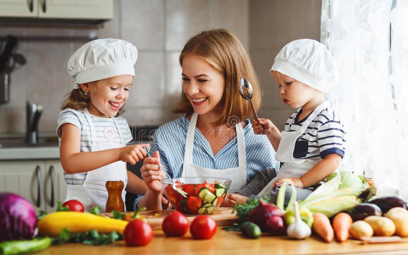 Healthy eating. Happy family mother and children prepares veg. Etable salad in kitchen royalty free stock photography