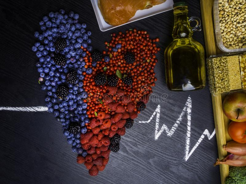 Healthy eating and heart health concept with a heart shaped with blueberries, raspberries, blackberries, cranberries, broccoli, stock photos