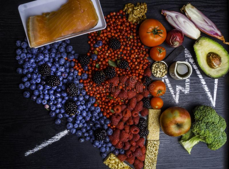 Healthy heart food, heart shaped. Healthy eating and heart health concept with a heart shaped with blueberries, raspberries, strawberries, avocado, nuts royalty free stock images