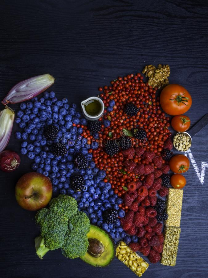 Healthy heart food, heart shaped. Healthy eating and heart health concept with a heart shaped with blueberries, raspberries, strawberries, avocado, nuts royalty free stock image