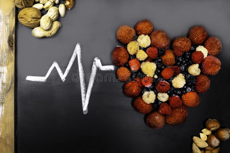 Healthy eating and heart health concept with a heart shaped with blueberries, raspberries, strawberries, nuts, full of vitamins. And antioxidants that can stock image