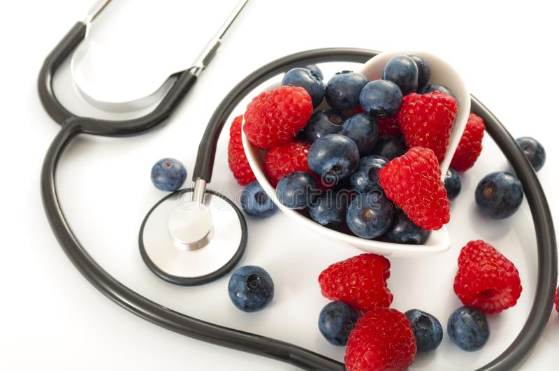 Healthy eating and heart health concept with a heart shaped bowl with mixed berries and a stethoscope each berry is packed full of. Vitamins and antioxidants stock image
