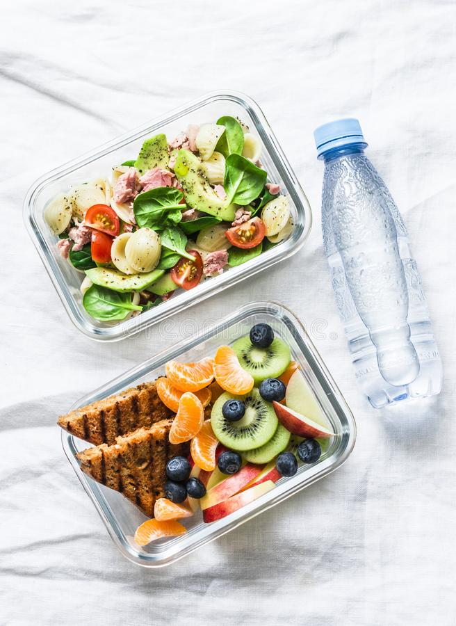 Healthy lifestyle concept. Office food lunch box - sweet and savory lunch, snack and clean water. Pasta, tuna, spinach, stock images