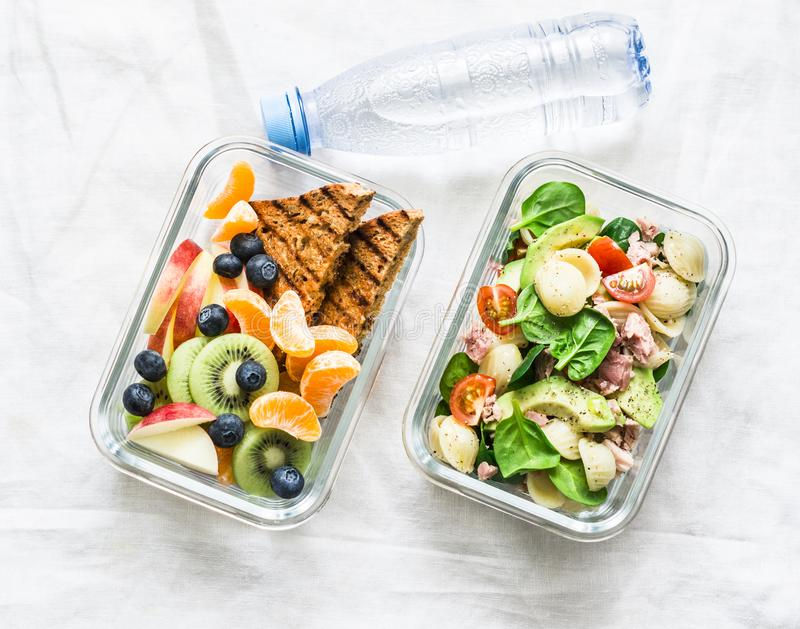 Healthy eating lifestyle concept. Office food lunch box - sweet and savory lunch, snack, clean water. Pasta, tuna, spinach, royalty free stock photos