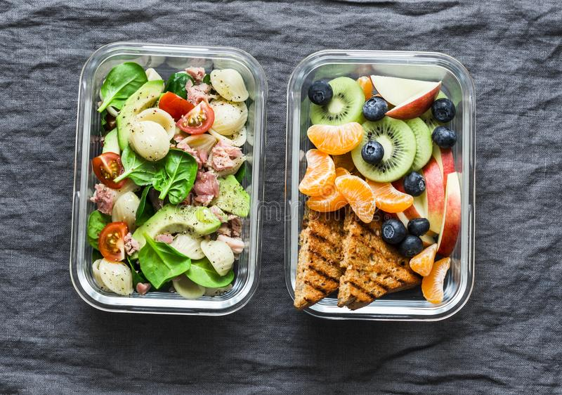 Healthy eating lifestyle concept. Office sweet, savory food lunch box. Pasta, tuna, spinach, avocado salad and fruit, peanut stock photography