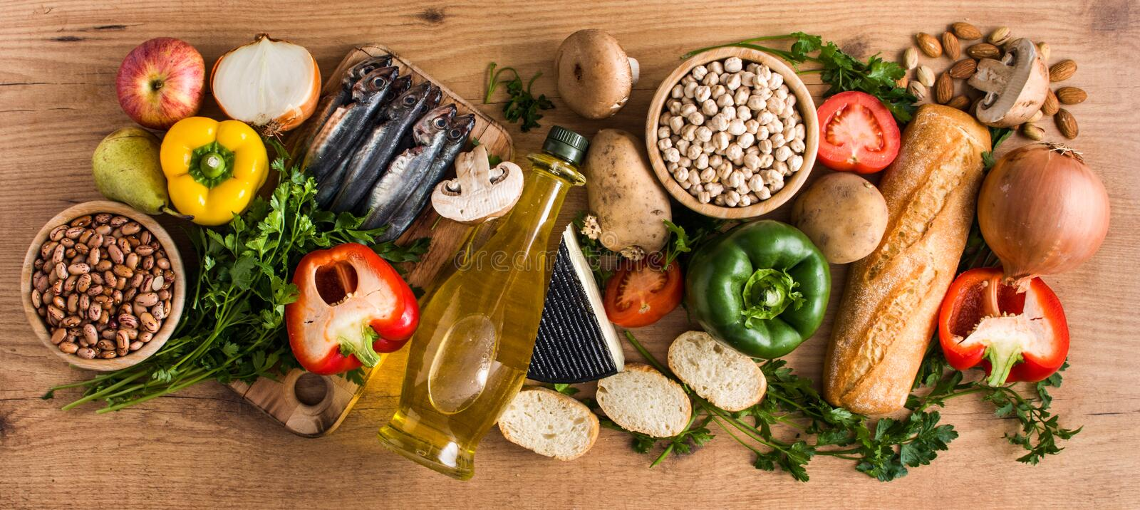 Healthy eating. Mediterranean diet. Fruit,vegetables, grain, nuts olive oil and fish on wood royalty free stock photography