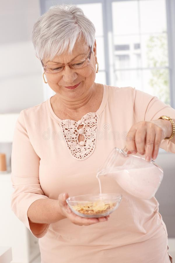 Healthy eating in old age. Elderly woman pouring milk over breakfast cereal, smiling stock photo