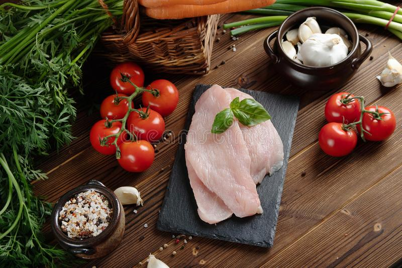 Healthy eating. Raw food concept. Vegetables and turkey fillet on wooden table. Top view royalty free stock photo