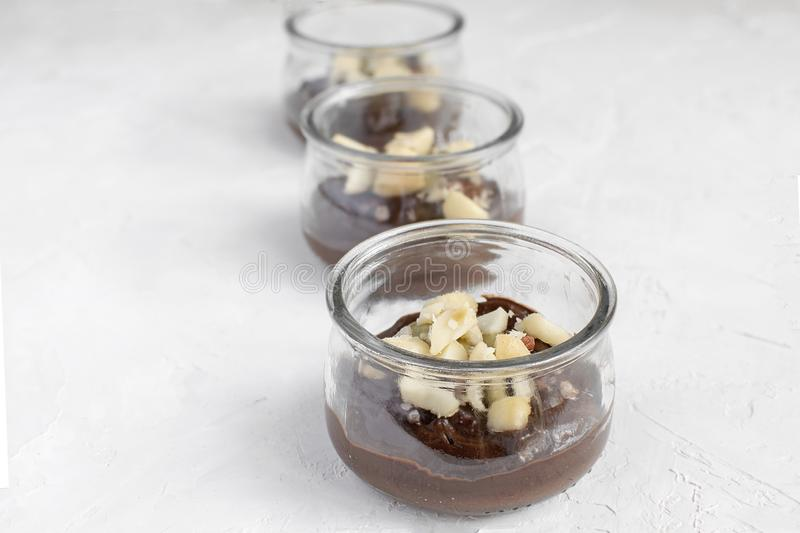 Healthy eating - vegan chocolate pudding made from avocado in glass jar with macadamia nuts on top, close-up, white background, royalty free stock photo