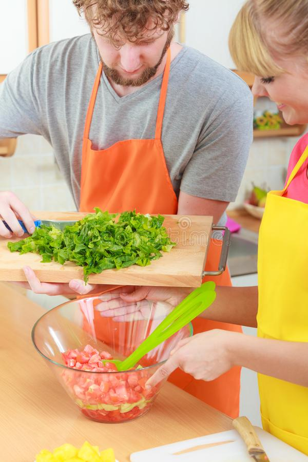 Couple preparing fresh vegetables food salad. Healthy eating, vegetarian food, cooking, dieting and people concept. Couple in kitchen at home preparing fresh royalty free stock photo